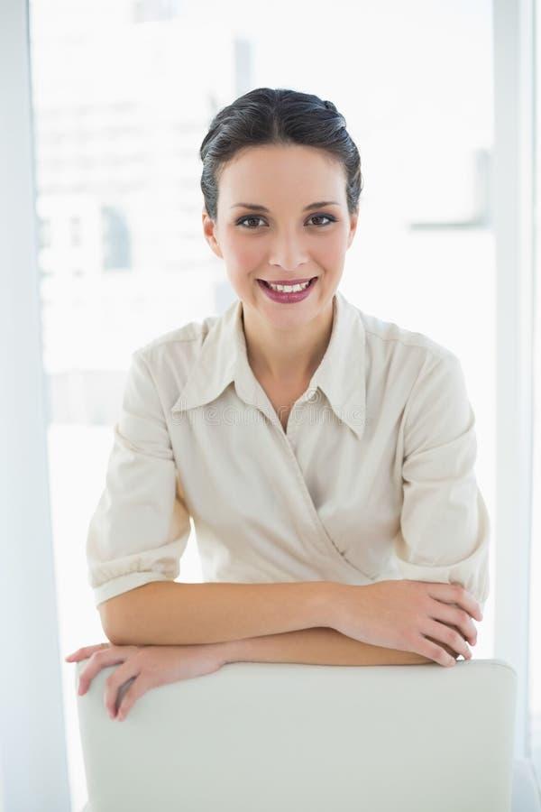 Donna di affari castana alla moda contenta che posa esaminando macchina fotografica immagine stock