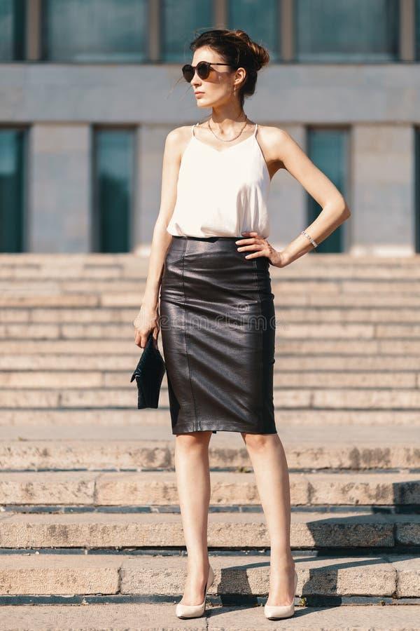 Donna di affari castana alla moda nella gonna di cuoio della matita e nella s immagini stock