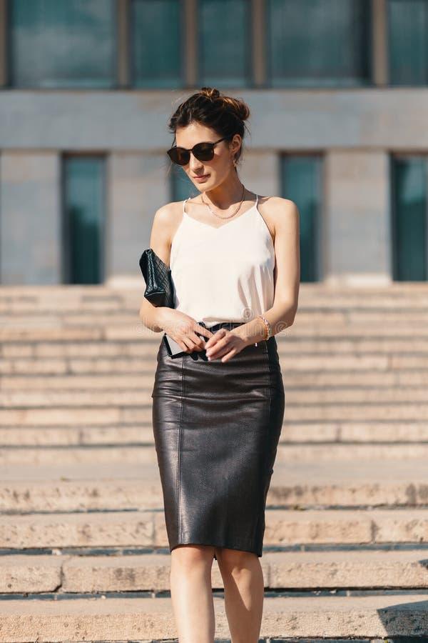 Donna di affari castana alla moda nella gonna di cuoio della matita e nella s fotografie stock libere da diritti