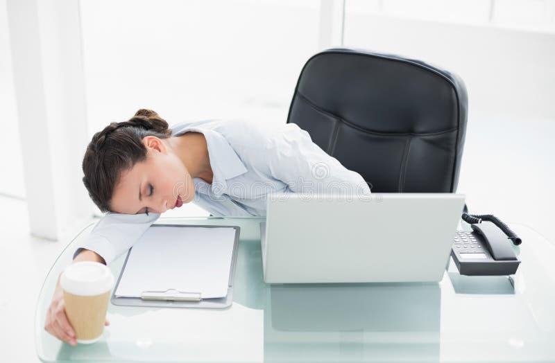 Donna di affari castana alla moda stanca che dorme sul suo scrittorio immagini stock libere da diritti