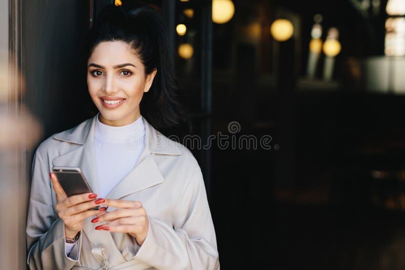 Donna di affari castana attraente che fa legare capelli scuri in cavallino fotografia stock