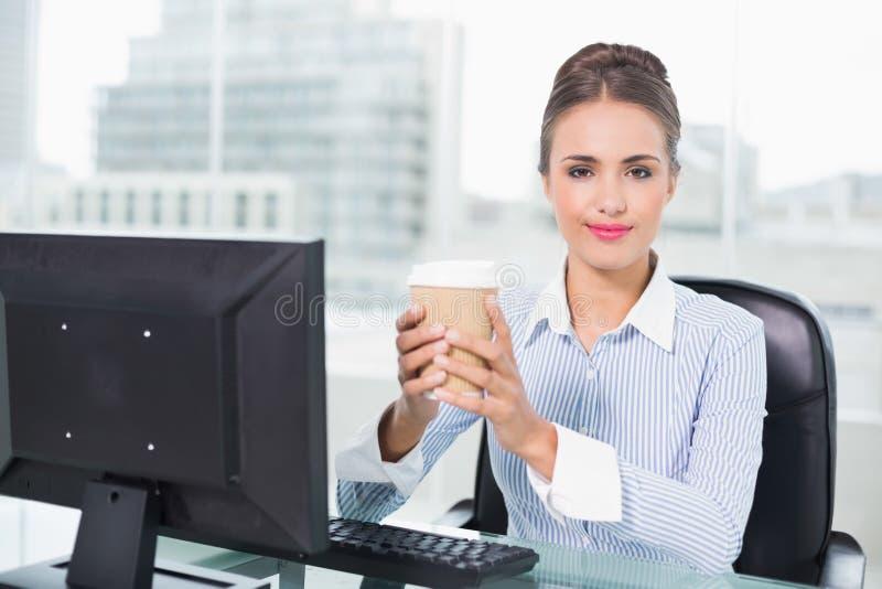 Donna di affari castana contenta che tiene tazza eliminabile fotografia stock libera da diritti