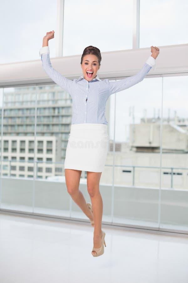 Donna di affari castana emozionante che salta e che incoraggia immagini stock