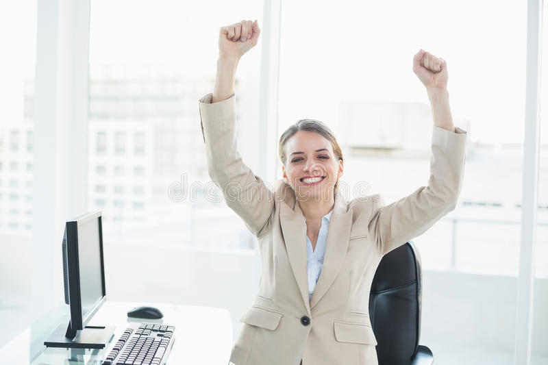 Donna di affari castana incoraggiante che si siede nel suo ufficio immagini stock