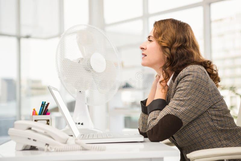 Donna di affari casuale che è raffreddata dal ventilatore immagini stock