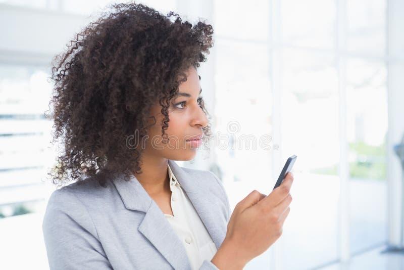 Donna di affari casuale che manda un sms sul telefono fotografia stock libera da diritti