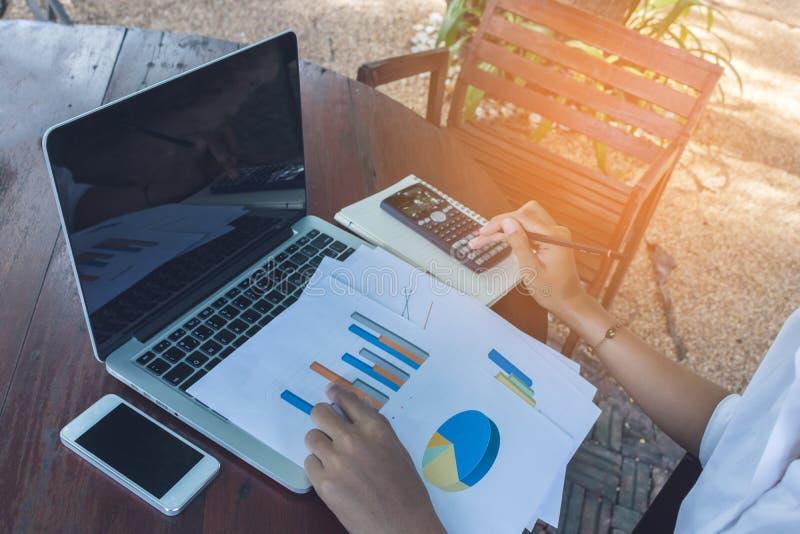 Donna di affari che analizza il documento del grafico finanziario con il tono dell'annata del telefono cellulare e del computer p fotografia stock