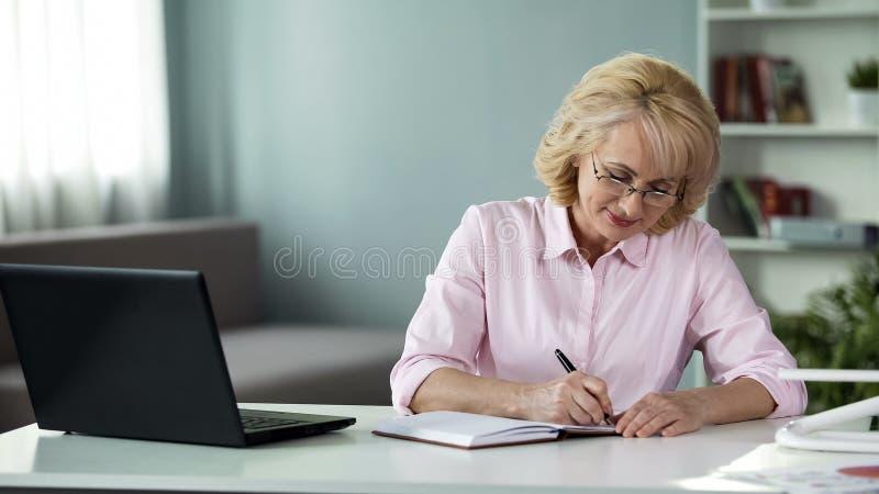 Donna di affari che annota al piano del taccuino per il prossimo avvenire, lavoro delle free lance fotografia stock
