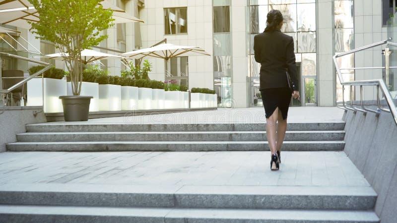 Donna di affari che cammina di sopra alla costruzione, alzante la scala di carriera, successo fotografie stock libere da diritti