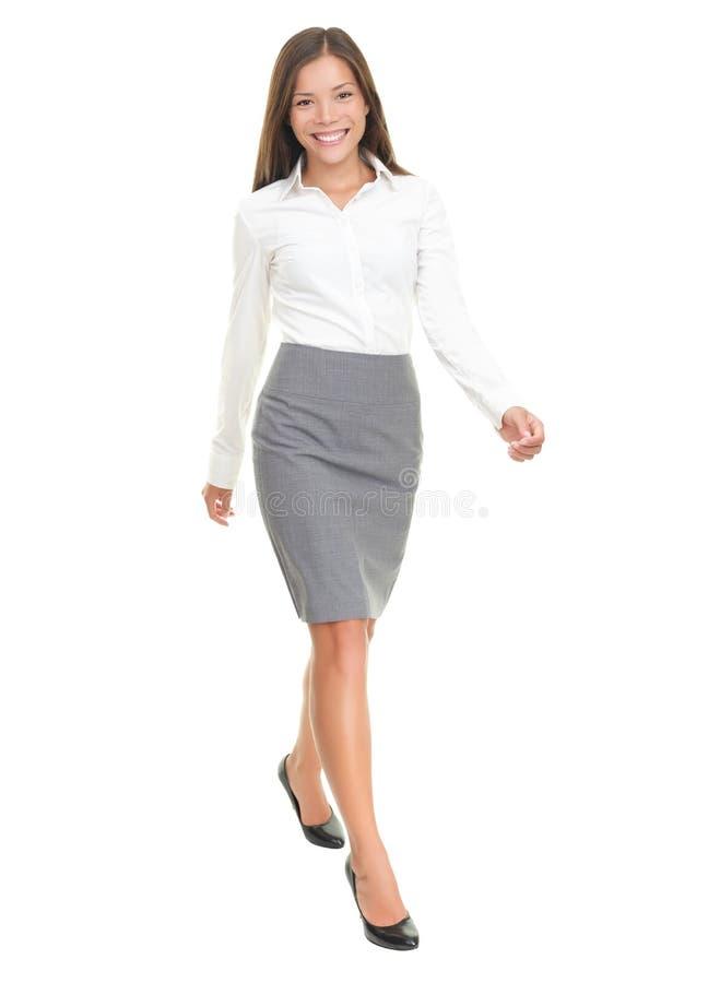 Donna di affari che cammina sulla priorità bassa bianca fotografie stock libere da diritti