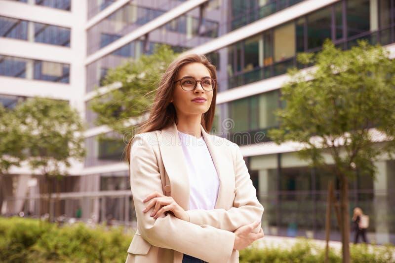Donna di affari che cammina sulla via fra gli edifici per uffici fotografia stock libera da diritti