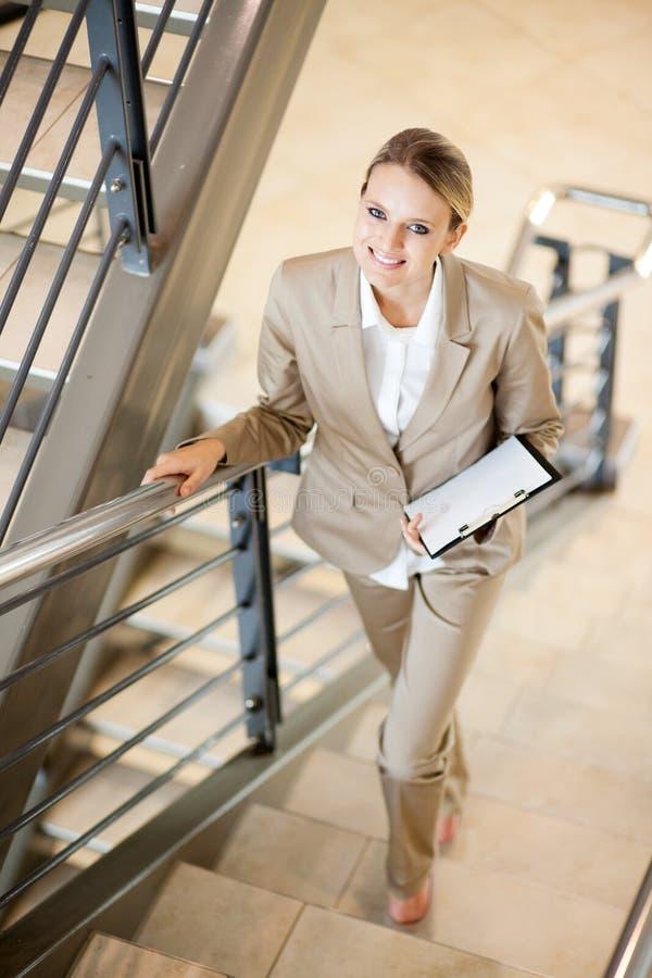 Donna di affari che cammina sulle scale fotografia stock