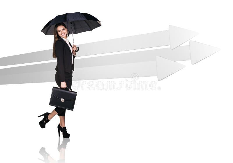 Donna di affari che cammina vicino alle grandi frecce grige immagine stock libera da diritti