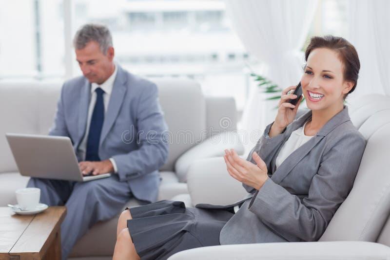 Donna di affari che chiama mentre il suo collega che lavora al suo computer portatile fotografie stock