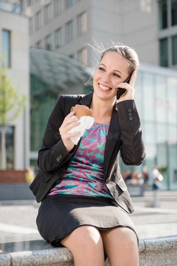 Donna di affari che chiama telefono e cibo immagine stock libera da diritti