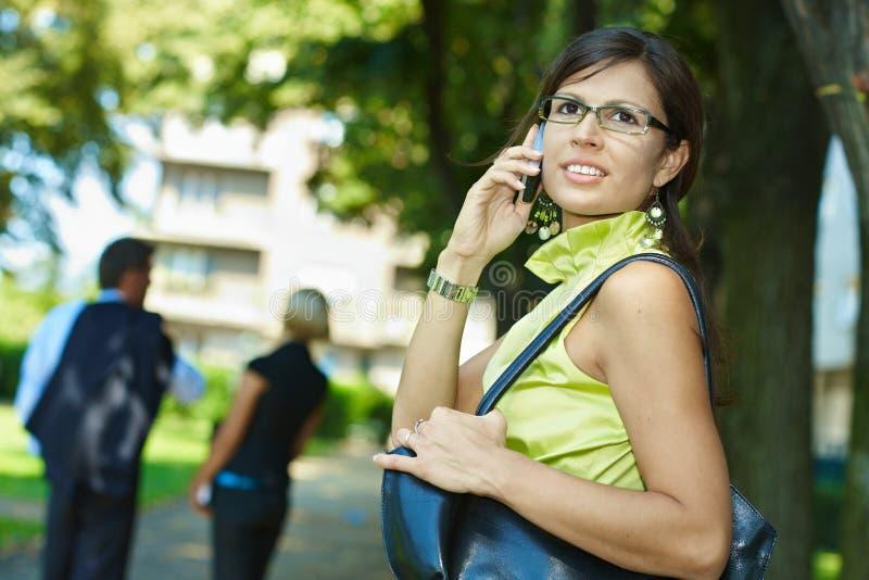 Donna di affari che comunica su esterno mobile fotografia stock