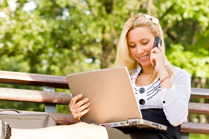 Donna di affari che comunica sul telefono in sosta fotografia stock libera da diritti