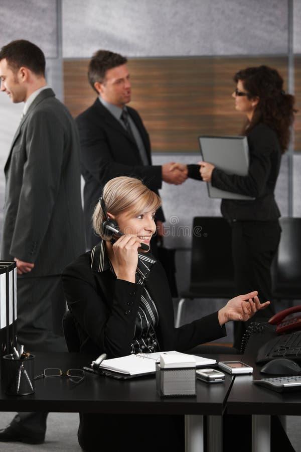 Donna di affari che comunica sulla cuffia avricolare immagini stock
