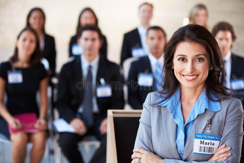 Donna di affari che consegna presentazione alla conferenza fotografia stock