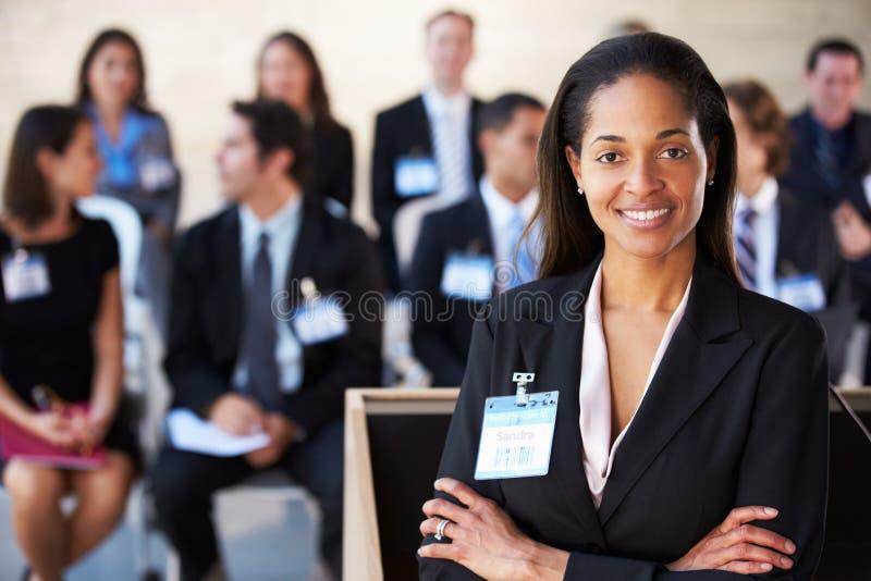 Donna di affari che consegna presentazione alla conferenza fotografie stock