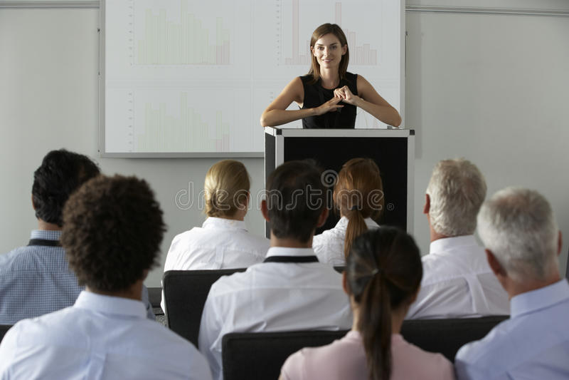 Donna di affari che consegna presentazione alla conferenza immagine stock