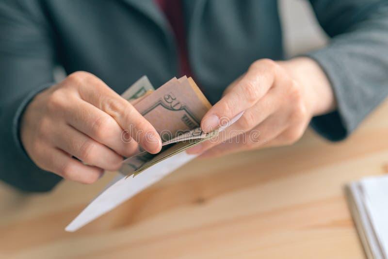 Donna di affari che conta le banconote del dollaro nell'ufficio di affari fotografia stock libera da diritti