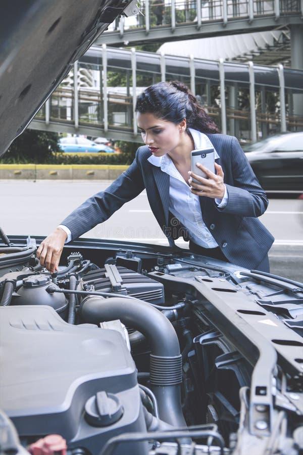 Donna di affari che controlla la macchina rotta dell'automobile fotografie stock