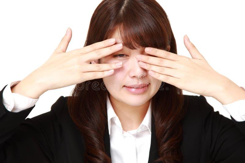 Donna di affari che copre il suo fronte di mani che sbirciano alla macchina fotografica tramite le sue dita immagini stock libere da diritti