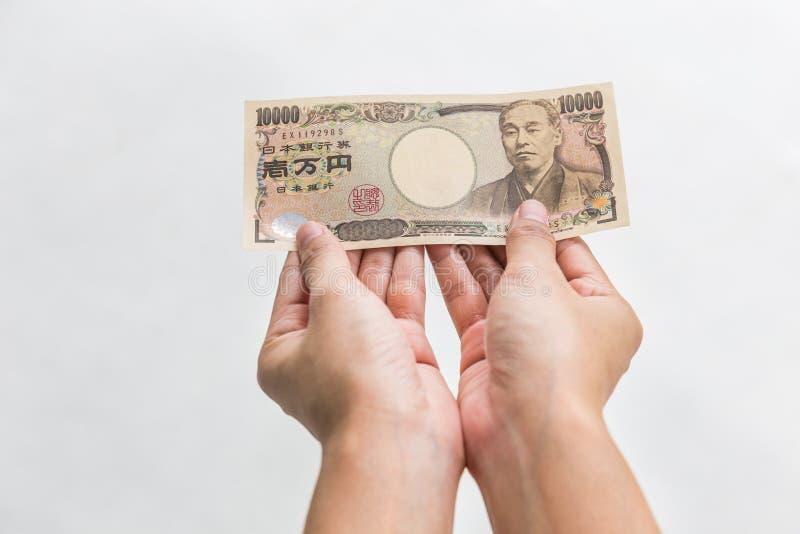 Donna di affari che dà soldi e che giudica 10.000 Yen giapponesi soldi in mano isolati su fondo bianco, Yen giapponese finanziari immagini stock