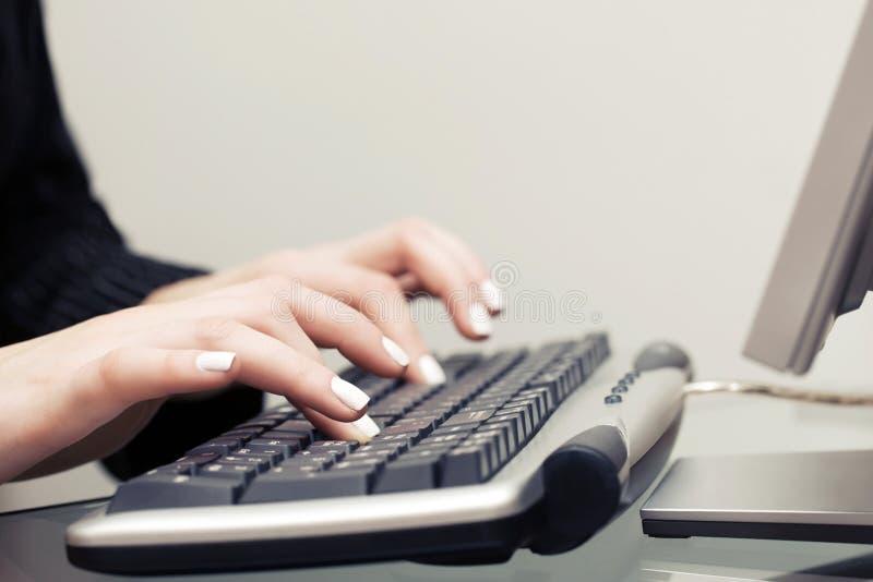 Donna di affari che digita sulla tastiera di calcolatore fotografia stock