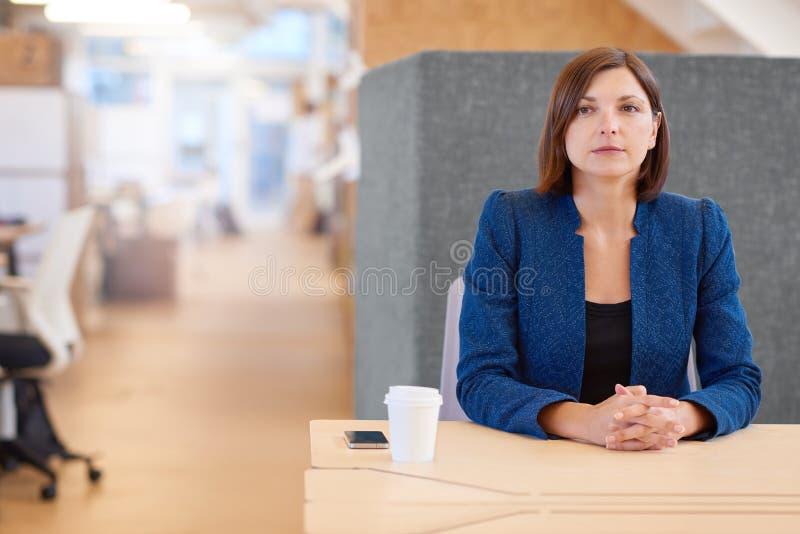 Donna di affari che distoglie lo sguardo mentre sedendosi al suo cubicolo d dell'ufficio fotografia stock libera da diritti