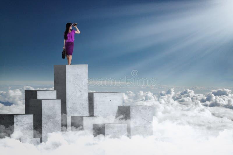 Donna di affari che esamina cielo blu con il binocolo immagini stock libere da diritti