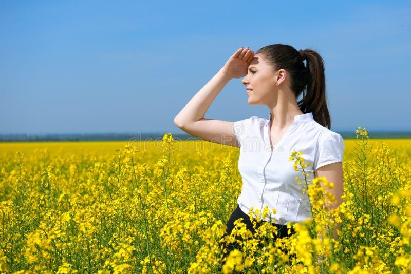 Donna di affari che esamina la distanza Ragazza nel giacimento di fiore giallo Bello paesaggio della molla, giorno soleggiato lum immagini stock