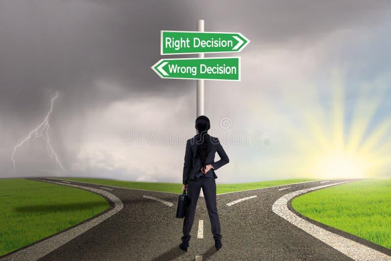 Donna di affari che esamina segno della destra contro la decisione sbagliata immagine stock libera da diritti