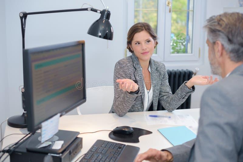 Donna di affari che fa gesto interrogante al collega maschio immagine stock libera da diritti