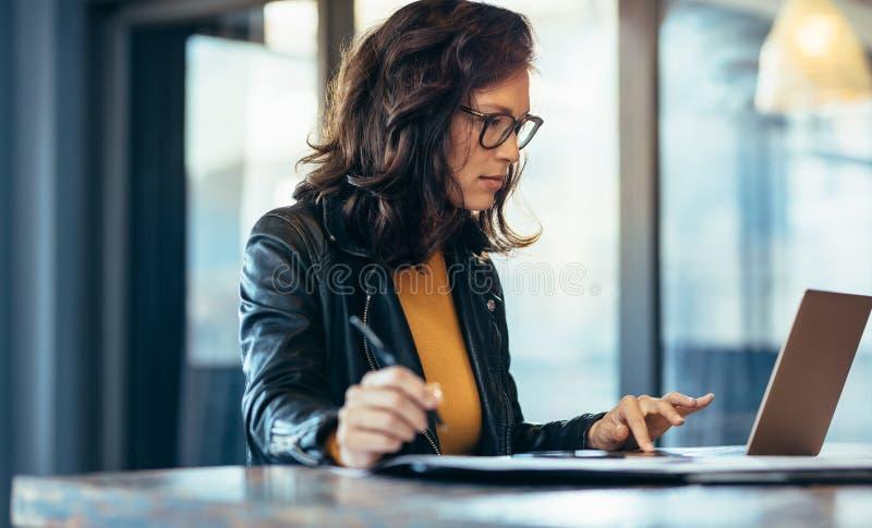 Donna di affari che fa le note che esaminano un computer portatile fotografia stock