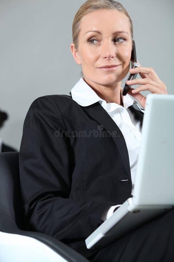 Donna di affari che fa una chiamata fotografia stock libera da diritti