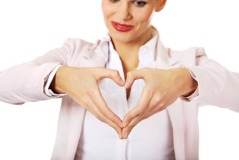 Donna di affari che fa una forma del cuore con le sue mani immagini stock