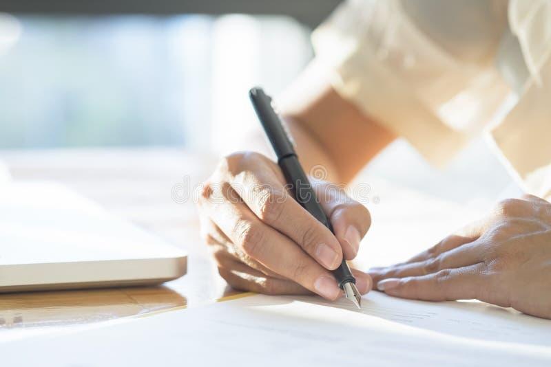 Donna di affari che firma un capitolato d'oneri che fa un affare fotografia stock