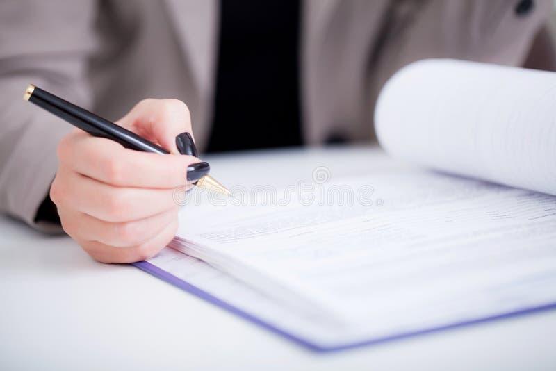 Donna di affari che firma un contratto sopra la riga dell'impronta fotografia stock libera da diritti