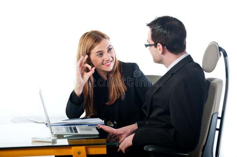 Donna di affari che gesturing OKAY al collega sul lavoro immagine stock