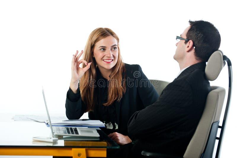 Donna di affari che gesturing OKAY al collega sul lavoro immagini stock libere da diritti