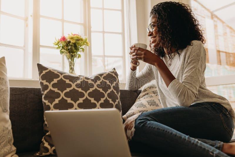 Donna di affari che gode di una tazza di caffè mentre lavorando al computer portatile immagine stock libera da diritti