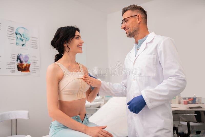 Donna di affari che ha fasciatura sul seno che prende per aggiustare immagine stock libera da diritti
