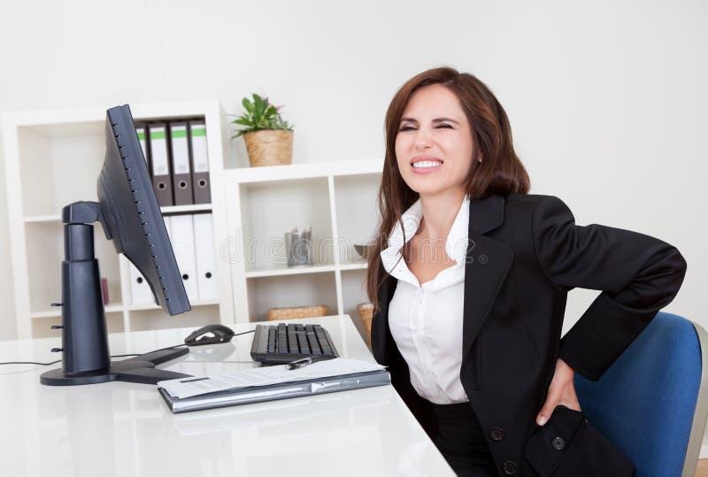 Donna di affari che ha mal di schiena sul lavoro fotografia stock