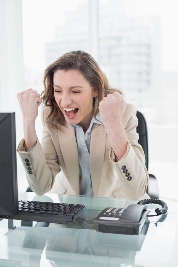Donna di affari che incoraggia con i pugni chiusi alla scrivania immagini stock libere da diritti