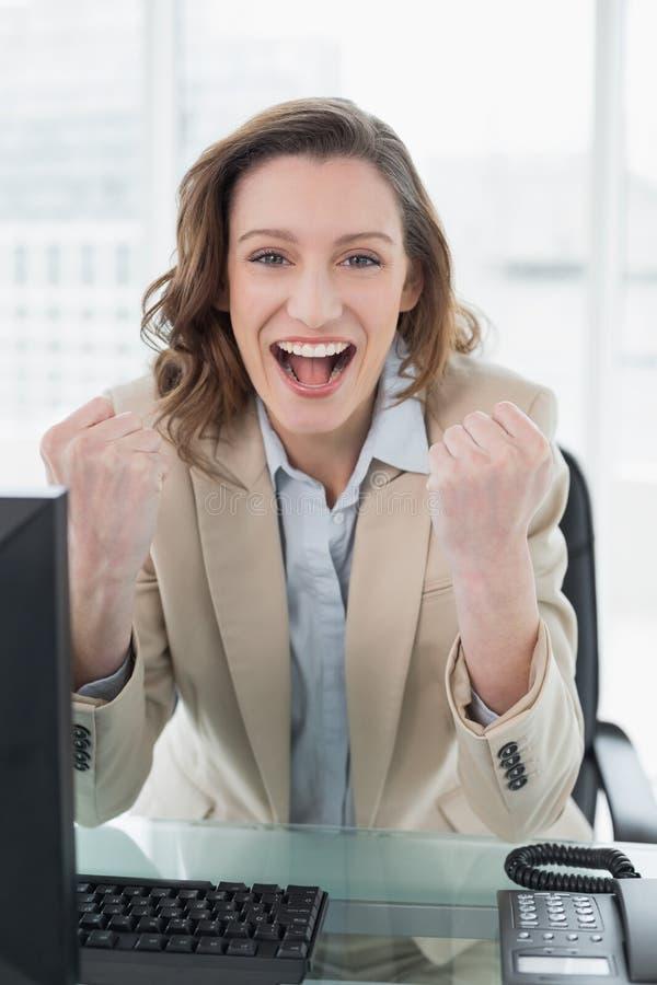 Donna di affari che incoraggia con i pugni chiusi in ufficio fotografie stock