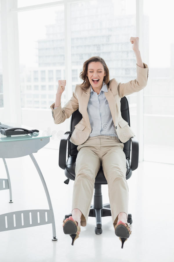 Donna di affari che incoraggia con le mani sollevate in ufficio immagine stock libera da diritti