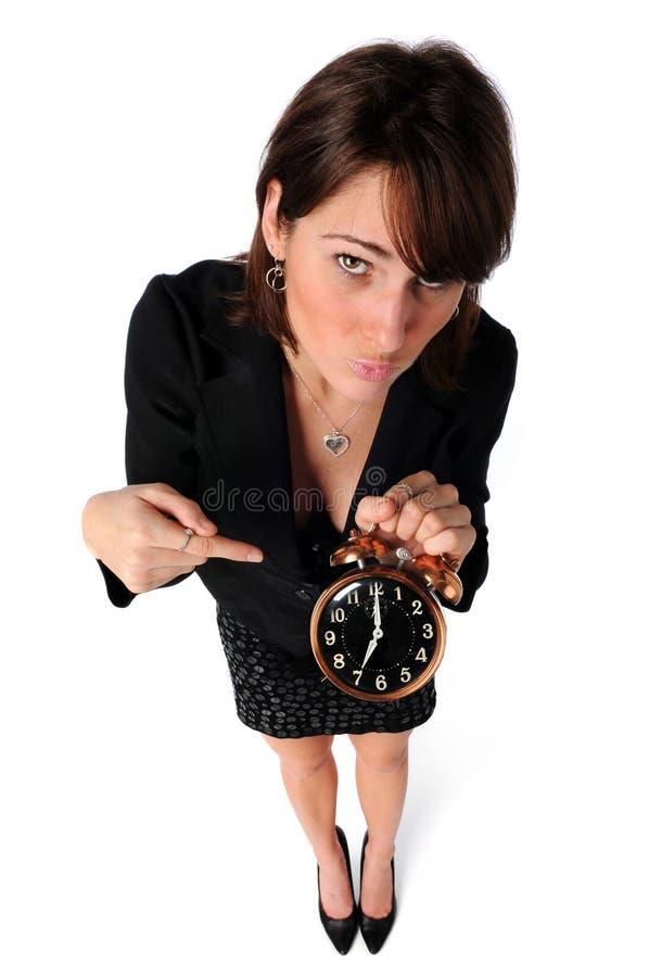 Donna di affari che indica l'orologio immagine stock