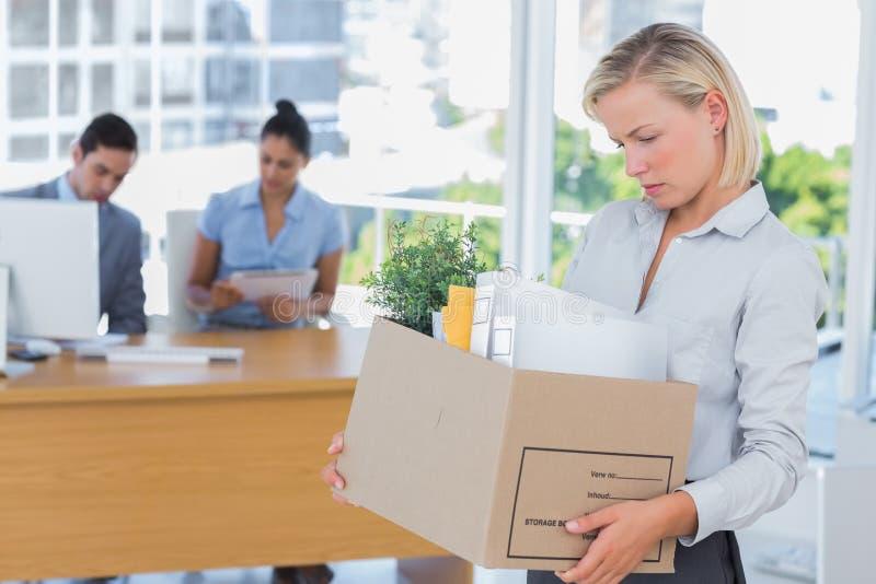 Donna di affari che lascia ufficio dopo essere stato licenziatoe fotografia stock